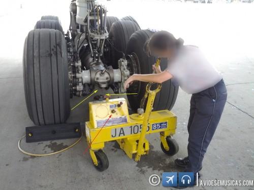 Mecânica posiciona o macaco sob o trem principal do 777